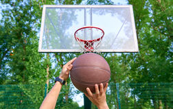 Hands throwing basketball ball into basket Royalty Free Stock Photography