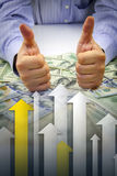 Hands with thumbs up, money and graph. Businessman's hands with thumbs up over bulk of money with arrows pointing upwards showing financial growth - Financial Royalty Free Stock Photos