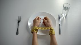 Hands tied with tapeline on empty plate, girl obsessed with counting calories. Stock photo stock photo