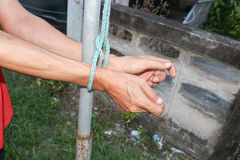 Hands tied up with rope, male with post steel hands tied rope. Select focus front hands and soft-focus background Stock Image