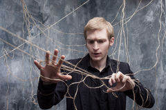 Hands are tied. Young man in  black suit got caught on the web. Concept of manipulation and slavery Stock Images