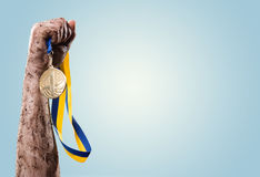 Hands tighten medal. Over blue Royalty Free Stock Photo