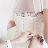 Hands Tightening A Corset To The Bride