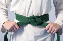 Hands tightening green belt on a teenage dressed Stock Images