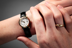 Hands and Time. Female hands checking the time on a wristwatch Stock Photos