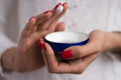 Hands to apply the cream out of the blue jar. Female hands with red nails applied the cream out of the blue jar Stock Image