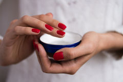 Hands to apply the cream out of the blue jar. Female hands with red nails applied the cream out of the blue jar Royalty Free Stock Image