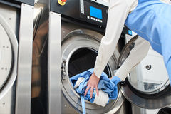 Hands to load the Laundry in the washing machine. At the dry cleaners royalty free stock photo