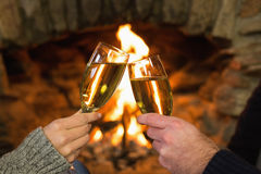 Hands toasting champagne flutes in front of fireplace Royalty Free Stock Photos