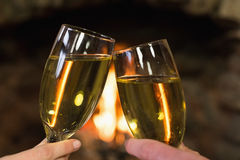 Hands toasting champagne flutes in front of fireplace Stock Images