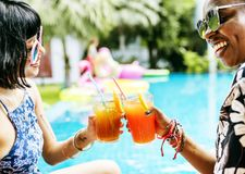 Hands toasting juice glasses by the pool summer time Stock Photos