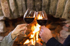 Hands toasting wineglasses in front of lit fireplace Stock Photo