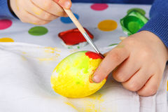 Hands of toddler boy painting colorful eggs for Easter hunt Stock Image