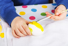 Hands of toddler boy painting colorful eggs for Easter hunt Royalty Free Stock Image