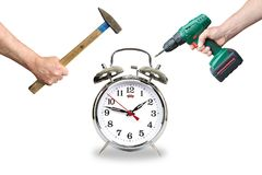 Hands with tool break the alarm clock Royalty Free Stock Photos