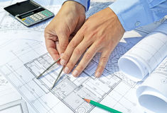 Hands with tool and project drawings Stock Photography