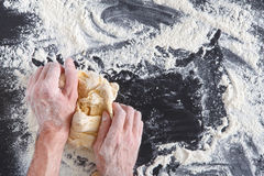 Hands top view knead dough on black background royalty free stock photo
