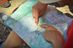 Hands on a topographic travel map Royalty Free Stock Photo