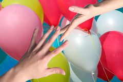 Hands touching on a background of balloons Royalty Free Stock Photos