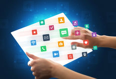 Hands touching a glass-like tablet with colorful icons Royalty Free Stock Image