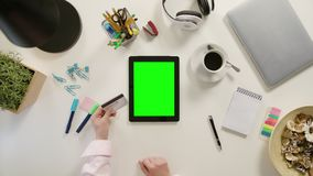 Hands Touching a Tablet and Holding a Credit Card. Hands touching a tablet with a green screen and holding a credit card. The tablet is on the white table. View Stock Photos