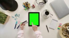 Hands Touching a Tablet and Holding a Credit Card. Hands touching a tablet with a green screen and holding a credit card. The tablet is on the white table. View Royalty Free Stock Photos