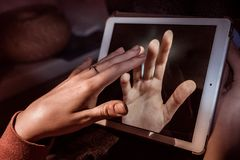 Hands touching through a tablet stock photo