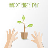 Hands try to holding young plant with Happy Earth Day text, pape Royalty Free Stock Image