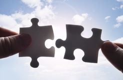 Hands trying to fit two puzzle pieces together stock photos