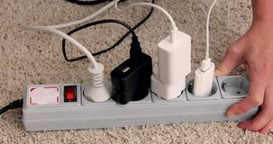 Hands turn off and unplug wires from electricity switch
