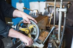 The hands of the turner rotate the wheel of the quill of the lathe. Royalty Free Stock Images