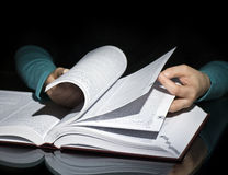 Hands turning the pages. Of a thick hard back book lying open, searching for information stock image
