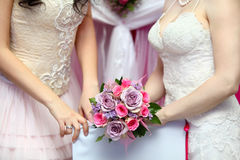Hands of two brides wearing dresses hold bouquet Royalty Free Stock Images