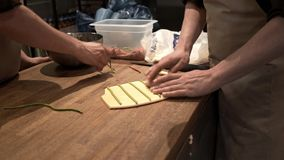 Two chefs placing green dough stripes on white dough in a restaurant. Hands of two chefs putting green dough stripes on white tortellini dough in an Italian stock video