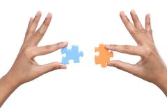 Hands with two different jigsaw puzzle pieces Royalty Free Stock Photos