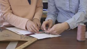 Hands of two female fashin designers, who are choosing the colour of the cloth for their model, close up. Two ladies are sitting at the wooden table with stock video footage