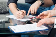 Two people signing a document Stock Photography