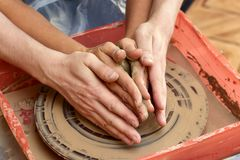 Hands of two people create pot, potter`s wheel. Teaching pottery Stock Photo