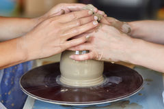 Hands of two people create pot, potter`s wheel. Teaching pottery Royalty Free Stock Photography