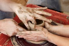 Hands of two people create pot, potter`s wheel. Teaching pottery. Hands of two people create pot on potter`s wheel. Teaching pottery, carftman`s hands guiding Stock Image