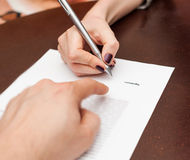 Hands of two people signed the document. In bank office Royalty Free Stock Photos