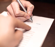 Hands of two people signed the document. Hands of two people signed the document in bank office Royalty Free Stock Photo