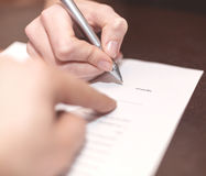 Hands of two people signed the document. Hands of two people signed the document in bank office Royalty Free Stock Image