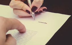 Hands of two people signed the document. Man and woman Royalty Free Stock Photos