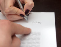 Hands of two people signed the document. Man and woman Stock Image