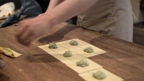 Two people making tortellini traditional Italian food. Hands of two unrecognizable middle age men making tortellini, a traditional Italian food. Concept of a stock video
