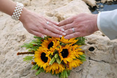 Hands with two white gold wedding rings on sunflower bouquet. Bride's and groom's hands with two white gold wedding rings on sunflower bouquet on the rock Stock Photo