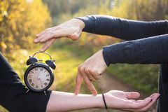 Hands of two women and a black vintage watch. Photo abstraction time stock image