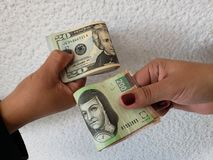 Hands of two women exchanging american dollar bills and mexican banknotes. Backdrop for announcements of trading and exchange, bank and commerce, background with royalty free stock photography