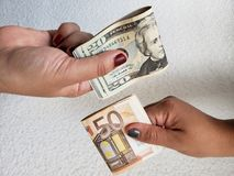 Hands of two women exchanging euro banknotes and american dollars bills. Backdrop for announcements of trading and exchange, bank and commerce, background with royalty free stock photo